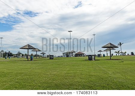 Green Lawn And Sunshades On Picnic Area On Beachfront