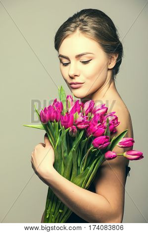 Spring portrait of young beautifull woman with tulip flowers on grey