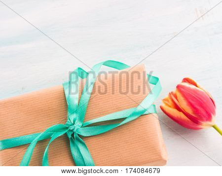 Gift box with green ribbon on pastel spring background. Copy space top view father's mother woman day Easter special occasion present