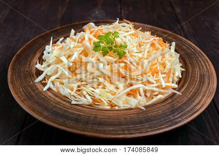 Salad of fresh cabbage and carrots in a clay bowl on dark wooden background. Lean vegetarian vitamin dish.