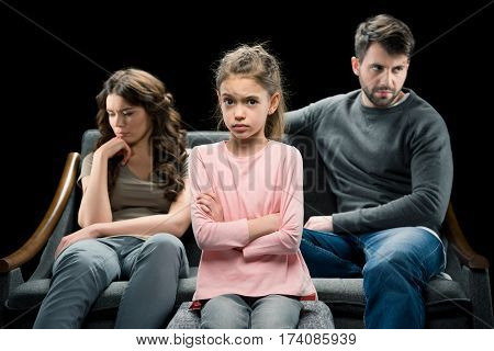 portrait of skeptical daughter and pensive parents behind on black divorce concept