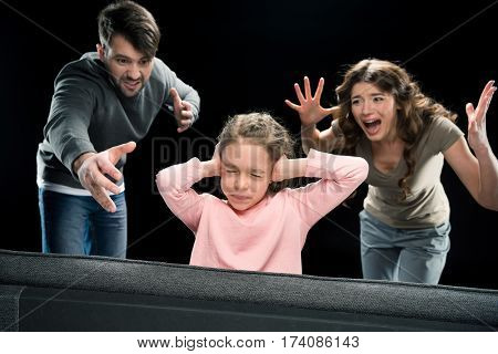 Emotional parents screaming at little daughter closing ears with hands family problems concept