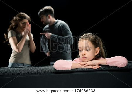 Upset little girl sitting on couch while parents quarreling family problems concept