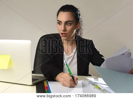 busy attractive woman in business suit working in stress writing desperate overwhelmed and overworked in office computer desk looking sad and depressed isolated background