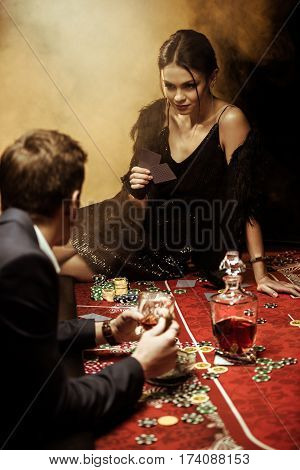 Gorgeous young woman sitting on poker table and playing poker with man in suit