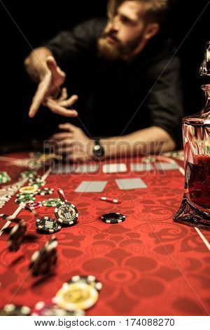 Bearded man throwing poker chips on table while playing poker