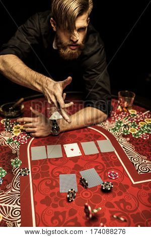 Emotional bearded man throwing poker chips on table while playing poker