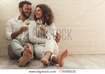 Beautiful Afro American couple in smart casual wear is holding glasses of wine hugging and smiling while sitting on the floor
