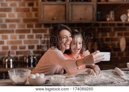 'Happy mother and daughter with flour on faces taking selfie