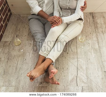 Cropped image of beautiful Afro American couple holding hands while sitting together on the floor