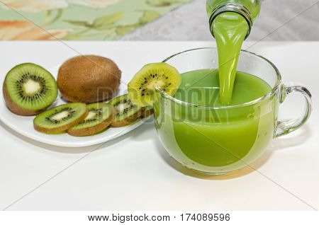 Fresh KIWI juice is poured from a bottle into a Cup, piece of fruit on the Cup and the plate nearby. Selective focus. Place for text.