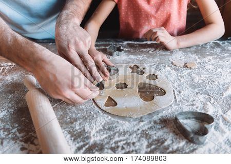 'Close-up partial view of father and daughter preparing cookies together Mothers day concept
