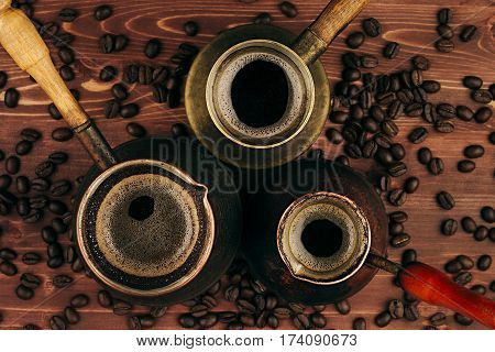 Hot coffee in shabby turkish pots cezve with crema beans on brown old wooden board background top view. Rustic style.