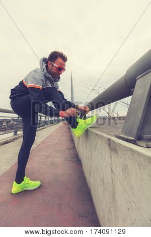 Urban jogger stretching / exercising and tying shoes on a big bridge.