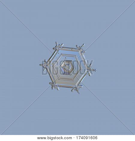 Macro photo of real snowflake, isolated on uniform blue background. This is small and simple hexagonal plate snow crystal with relief central hexagon.
