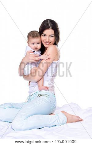 Happy young mother tenderly embracing her small baby. Family concept. Healthcare, pediatrics. Isolated over white.