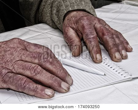 Closeup of the wrinkled hands of an old caucasian man holding pen and paper wearing a green sweater
