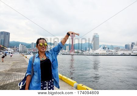 Thai woman pose for portrait with Kobe port tower in Meriken park near MOSAIC shopping mall at Kobe Harborland on July 9 2015 in Kobe Japan