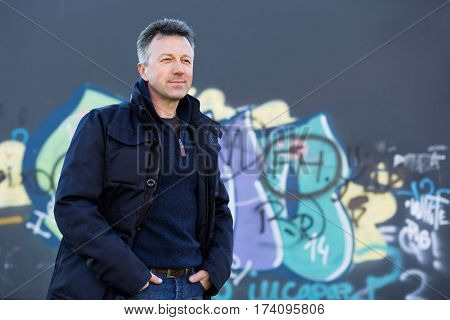 Handsome happy smiling man. Outdoor winter male portrait. Attractive confident middle-aged man in sunglasses posing in city park over grunge abstract art graffiti wall, image toned.