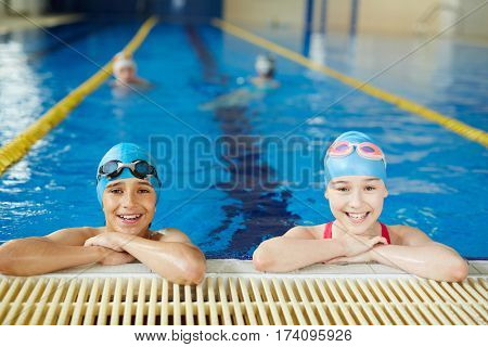 Two schoolchildren smiling brightly looking at camera at border of clear blue water swimming pool