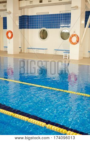 Shot of empty indoor sports swimming pool with lanes separated by yellow lines on still clear water surface and life rings hanging beside it