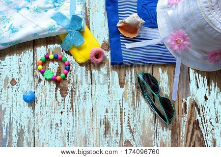 Overhead view of traveler's casual outfits Essential outfit of traveler Travel stuff on wood broad Summer vacation concept background