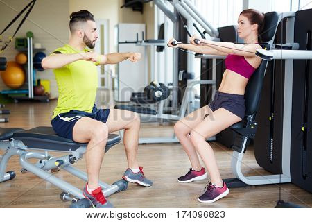 Working out in gym: Side view of beutiful yong woman doing arm excercise on cable machine with personal fitness instructor assisting her