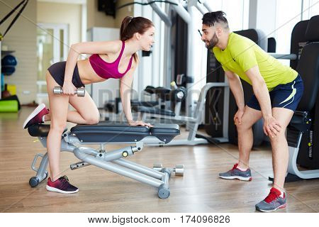 Working out in gym: Beutiful yong woman doing dumbbell excercise leaning on bench seductively while muscular trainer watching and assisting her