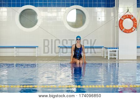 Healthy young woman wearing one piece swimsuit and goggle sitting at border of indoor swimming pool and looking at camera cherfully