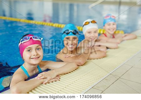 Group of cheerful school kids smiling looking to camera at border of swimming pool during practice