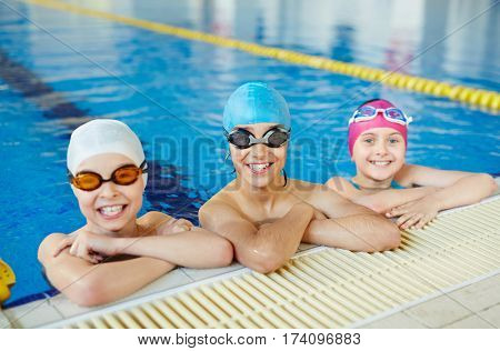 Three healthy smiling children looking to camera wearing swimming goggles and caps in water at tiled border of blue clearwater swimming pool