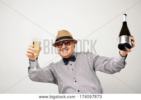 Waist-up portrait of dressed-up elderly man dancing with glass and bottle of champagne and smiling at camera cheerfully