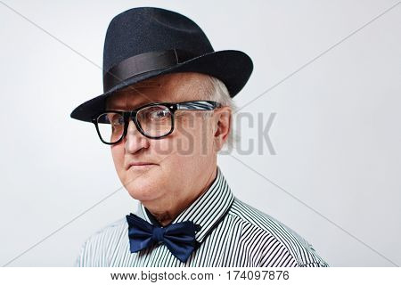Headshot of stylish senior man in black hat and striped shirt with bowtie looking at camera disapprovingly isolated on white background