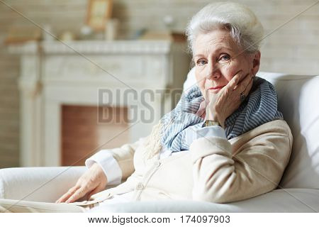Pretty elderly woman in white shirt and beige cardigan leaning on elbow and looking at camera with slight smile