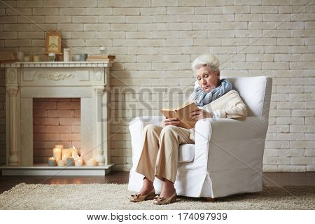 Senior woman in beige clothes relaxing at home in the evening with detective novel, fireplace with decor elements observed on background