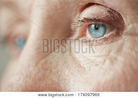Extreme close-up shot of sad blue eyes on wrinkled female face looking into the distance
