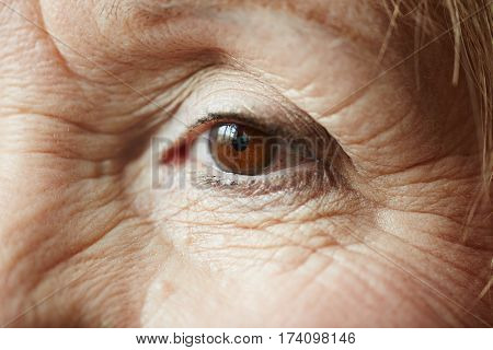 Extreme close-up shot of old female eye with minimal make-up looking away pensively