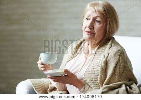 Melancholic senior woman with plaid on shoulders holding coffee mug in one hand and saucer with cookies in other while relaxing in living room