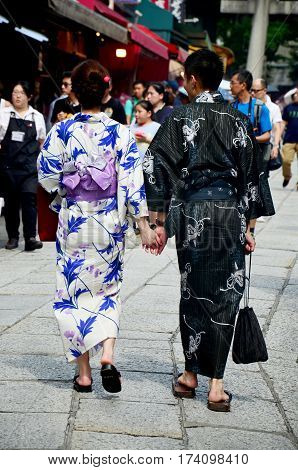 Japanese People Wear Traditional Japanese Clothing (kimono And Yukatas) Walking Hand In Hand On Stre