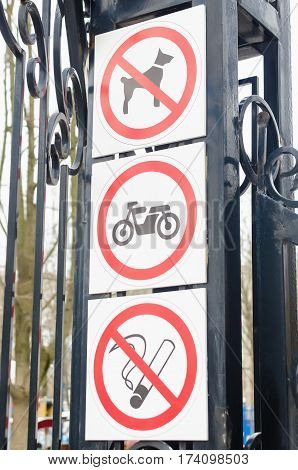 Prohibition signs no Smoking no drinking, not dogs, You can't ride a bike in the Park on a background of birch trees