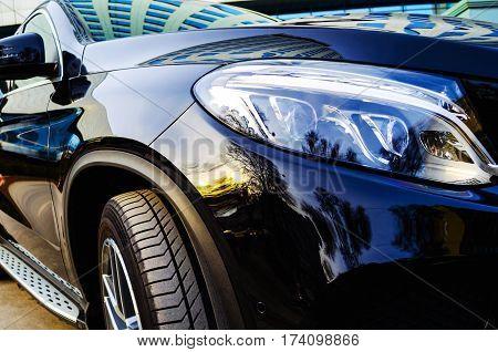 Closeup of the headlights of a black car