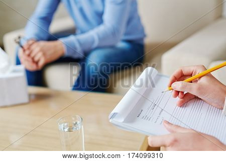 Process of filling in medical card of depressed patient in psychologists office, close-up shot