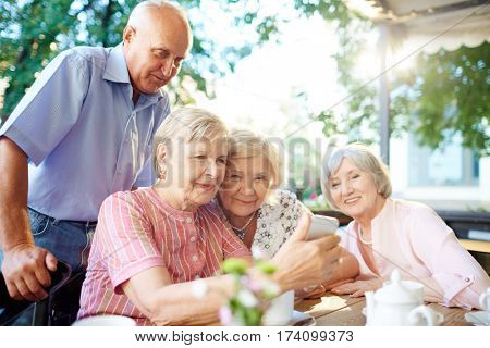 Modern seniors gathered together in patio and surfing the net with smartphone, table laid for tea-drinking