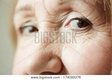 Extreme close-up shot of deep dark brown eyes with wrinkles around them looking at camera