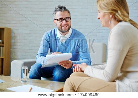 Bearded middle-aged psychologist having session with female patient and making notes in his private consulting room