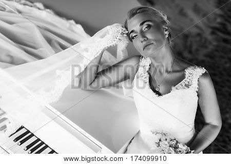 Bride Looks Marvelous Standing Behind A Piano And Holding Her Head Thoughtfull