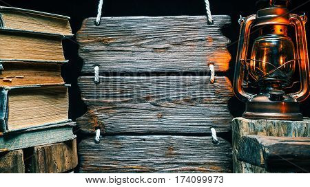 Old books stack with kerosene lamp and triple wooden signboard. Isolated over black