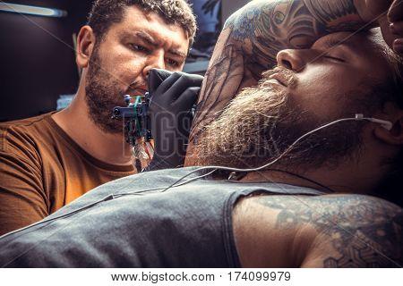 Professional tattooist making a tattoo in tatoo salon./Tattoo specialist posing in tattoo studio.