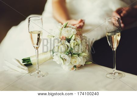 Two Wineglasses With Champagne Stand On The Table Behind A Wedding Bouquet