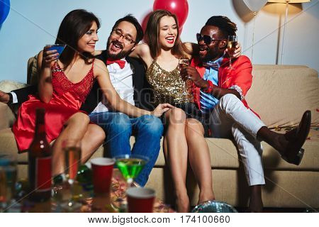 Four stylish best friends slightly embracing each other while sitting on comfortable couch and laughing at something, full-length portrait